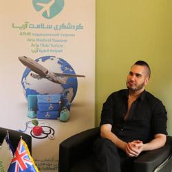 ايان من استراليا يحمل علم شركة آريا مدتور معبراً عن رضاه عن الخدمات التي تلقاها