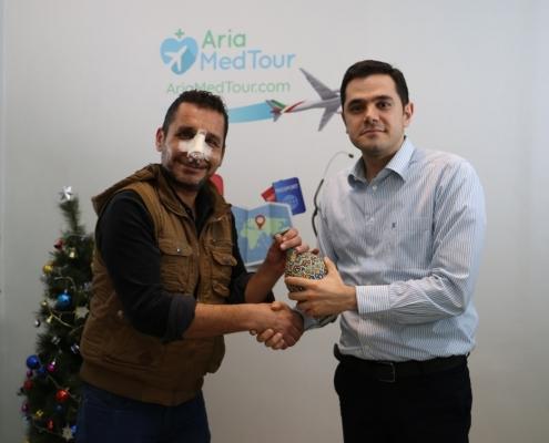 مريض من العراق يتلقى هدية تذكارية من شركة آريا مدتور بعد إجراء عملية الانف في ايران