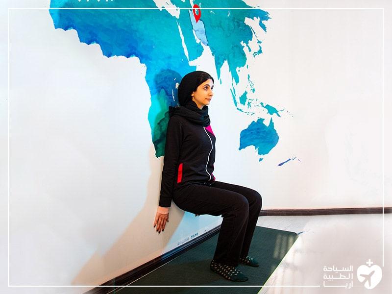 تمرين الجلوس استناداً إلى الجدار لتخفيف ألم الظهر الناتج عن الانزلاق الغضروفي