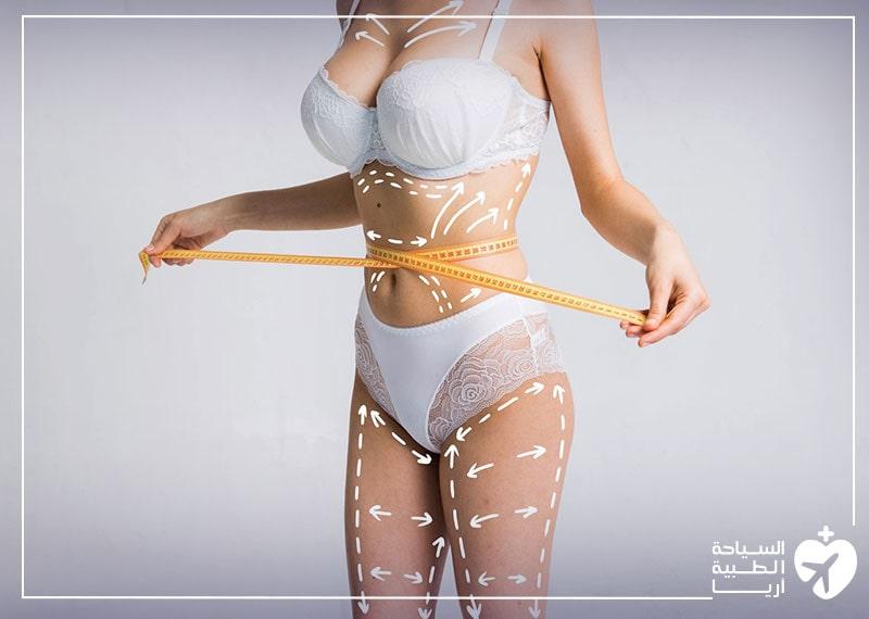 سيدة تقيس حجم بطنها وتستعد لشفط الدهون