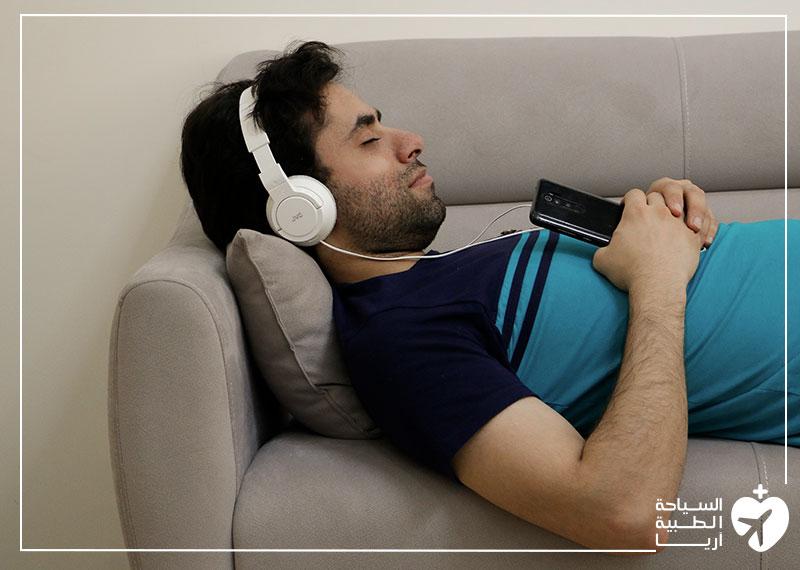 رجل يستمع إلى الموسيقى ليسترخي ويقلل من قلقه وتوتره قبل الجراحة