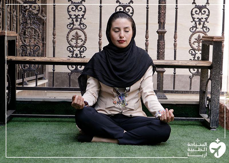 امرأة تجلس على العشب وتحاول ممارسة اليوجا والتأمل لتقليل القلق والتوتر قبل الجراحة
