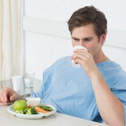شاب يرتدي حلة زرقاء يأكل ويشرب قبل الجراحة