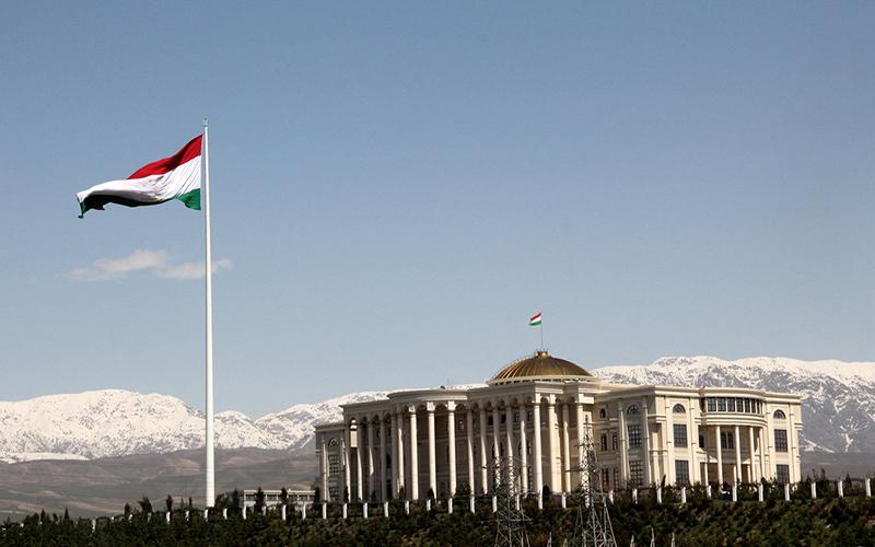 ساختمان کاخ ملل در دوشنبه در کنار پرچک تاجیکستان و تصویر کوه های پوشیده از برف در پس زمینه