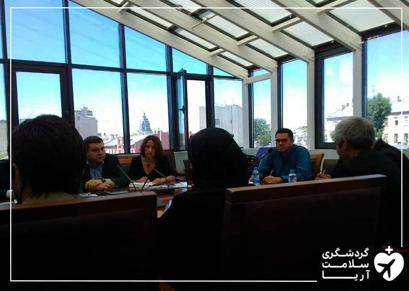 محمد نصری و تعدادی خانم و آقا در یک اتاق با پنجره های زیاد، دور یک میز جلسه برگزار کرده اند و در حال مذاکره هستند