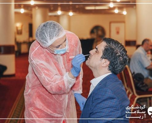 یک خانم پرستار با لباس صورتی رنگ، در حالی که ماسک و کلاه و دستکش پوشیده است، از یک آقا که کت و شلوار آبی به تن دارد تست کرونا می گیرد.