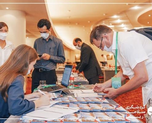 یک خانم پشت میز نشسته و سه اقا دور میز ایستاده اند و در حال مطالعه دستاوردهای ایران هستند.