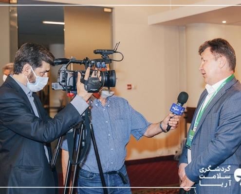 سه آقا در یک سالن حضور دارند و یک نفر خبرنگار، با یک میکروفن آبی رنگ در حال گرفتن مصاحبه از یک نفر دیگر است و فرد سوم با دوربین از آنها فیلم می گیرد