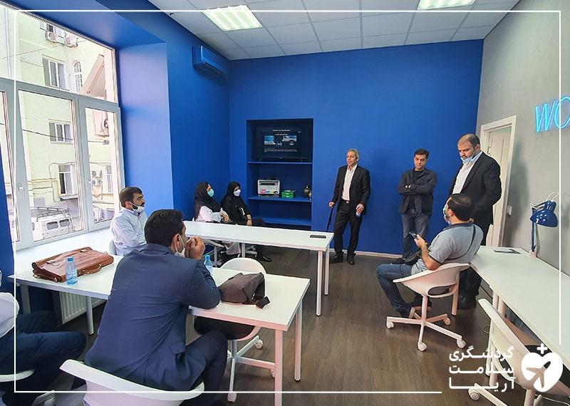 تعدادی آقا در یک اتاق با دیوارهای آبی رنگ پشت میز و صندلی نشسته اند و در حال صحبت کردن هستند.
