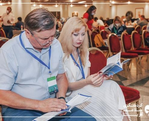 یک خانم و یک آقا روی صندلی نشسته اند و در حال مطالعه لیست دستاوردهای ایران هستند