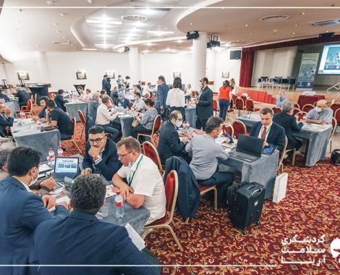 تعداد زیادی شرکت کننده در نشست B2B در یک سالن بزرگ دور میزهای چهارنفره نشسته اند