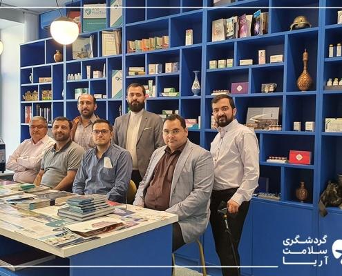 شش آقا داخل یک اتاق هستند که سه نفر روی صندلی نشسته اند و سه نفر ایستاده اند و پشت سر آنها قفسه دستاوردهای ایران قرار داد و جلوی آنها یک میز بزرگ