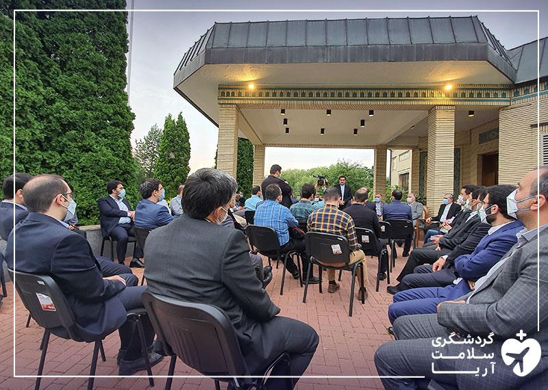 تعدادی آقا در حیاط ساختمان سفارت ایران در روسیه روی صندلی نشسته اند و جلسه در حال برگزاری است.