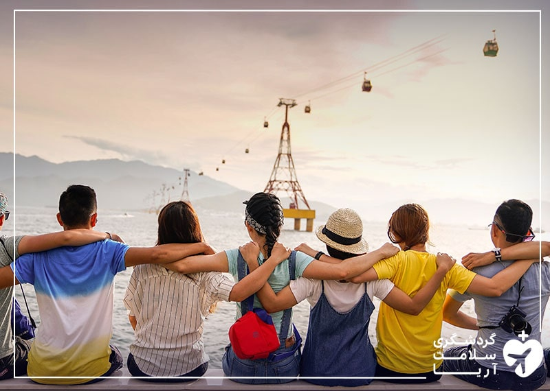 تعدادی توریست به صورت دوستانه در کنار یگدیگر نشستهاند و صنعت گردشگری در حال جان گرفتن است