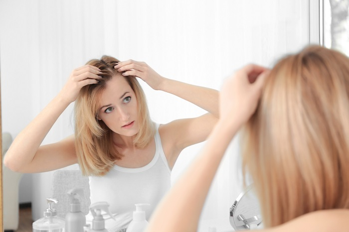 Young woman with hair loss problem looking in mirror at