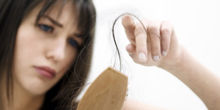 Portrait of a young woman brushing her hair fiddling with lost hair strand stuck in brush