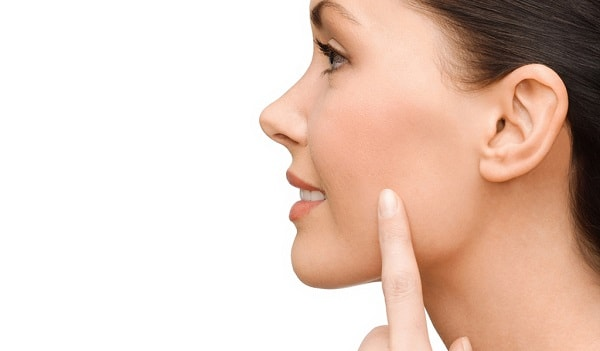 woman pointing to her cheek without excess fat