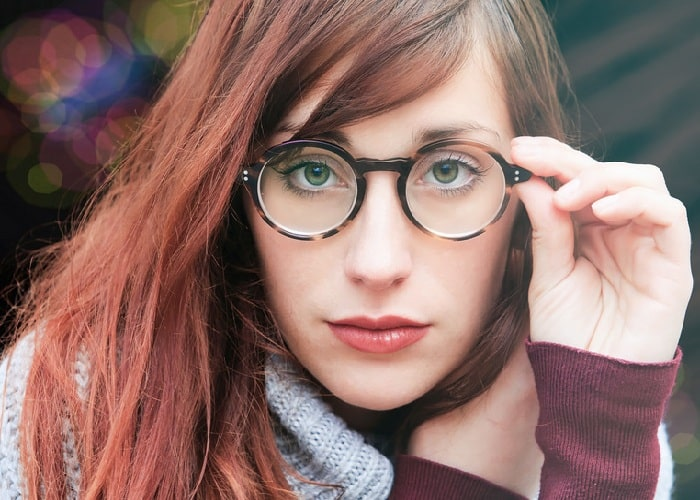 girl with brown hair grabbing her eyeglasses with hand