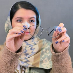 Iranian girl with Hijab and nose splint holding her eyeglasses after her nose job