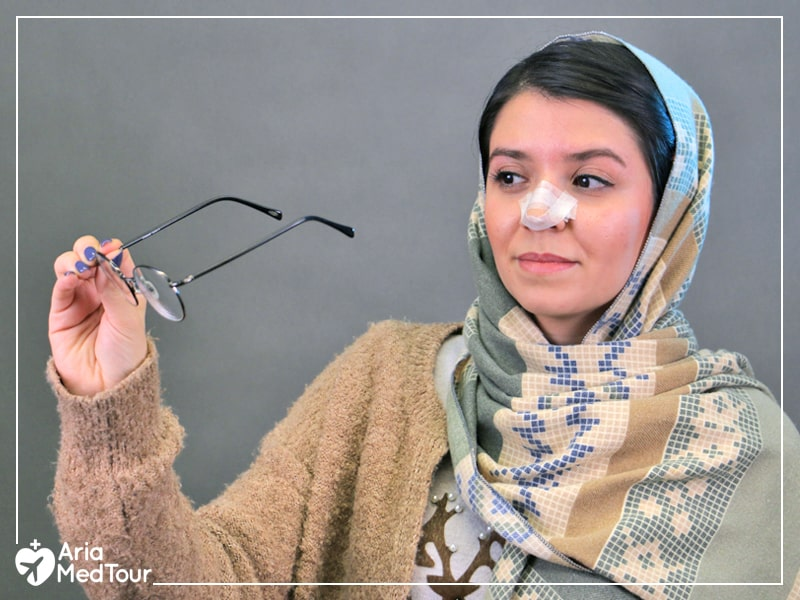 Iranian girl holding her eyeglasses wondering whether to wear glasses after her nose job