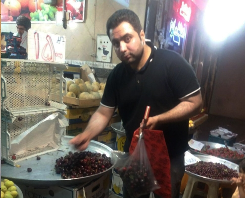 tourist buying cherries in Iran tajrish bazaar