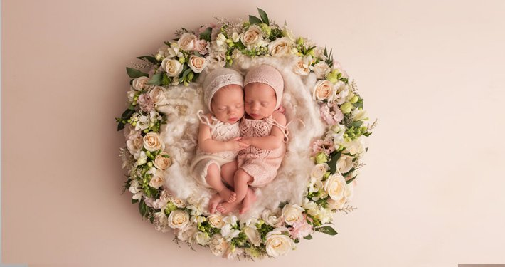 twin babies sleeping in the middle of flowers