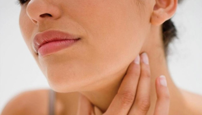 woman touching her chin and neck