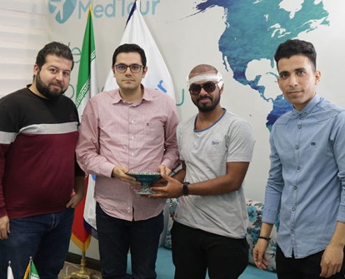 Omani hair transplant patient Saeed and AriaMedTour staff posing for a photo at AriaMedTour office in Tehran