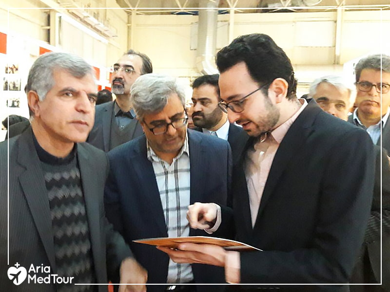 President of AriaMedTour, Hadi Shajari, speaking with two people in a crowd