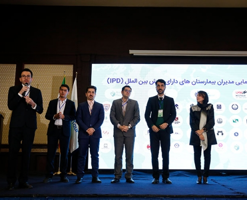 AriaMedTour's president Hadi Shajari giving a lecture during the health tourism conference held in Tehran, with other AriaMedTour'sstaff seen in background