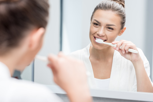 woman brushing her teeth in front of a mirror to keep her dental bridges healthy