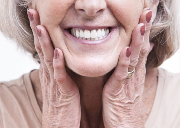 happy old woman showing her mouth after getting dentures in iran