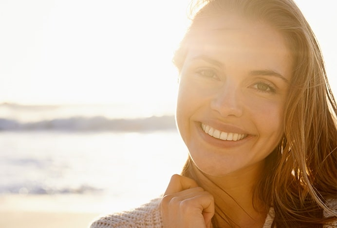 happy woman with a shiny skin smiling to the camera while sun rays are seen from behind her