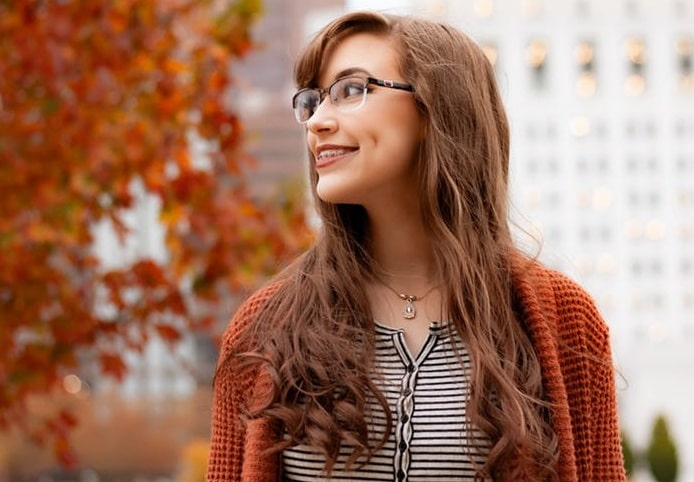woman with brown hair and dental braces standing in the street in autumn