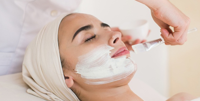 woman lying and closing her eyes while getting chemical peel by dermatologist in a beauty clinic