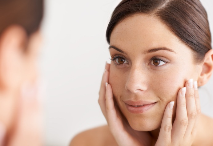 A young woman looking at her reflection in the mirror with her hands on her face happy with her cosmetic results