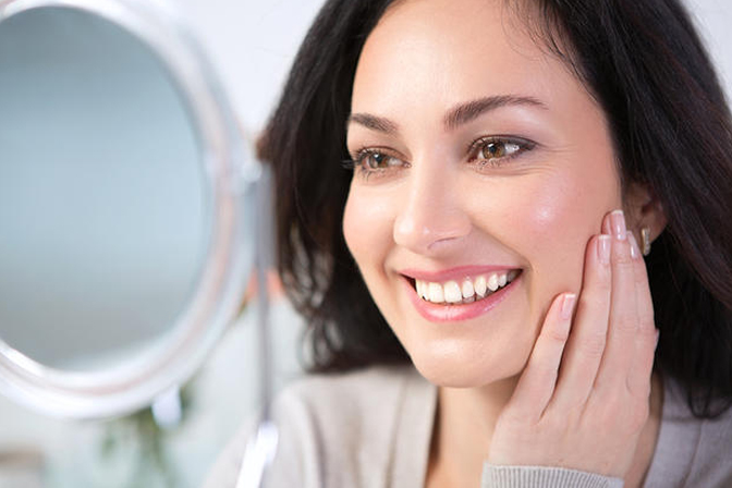 smiling woman holding a mirror in front of her face and touching her fresh skin after ultherapy