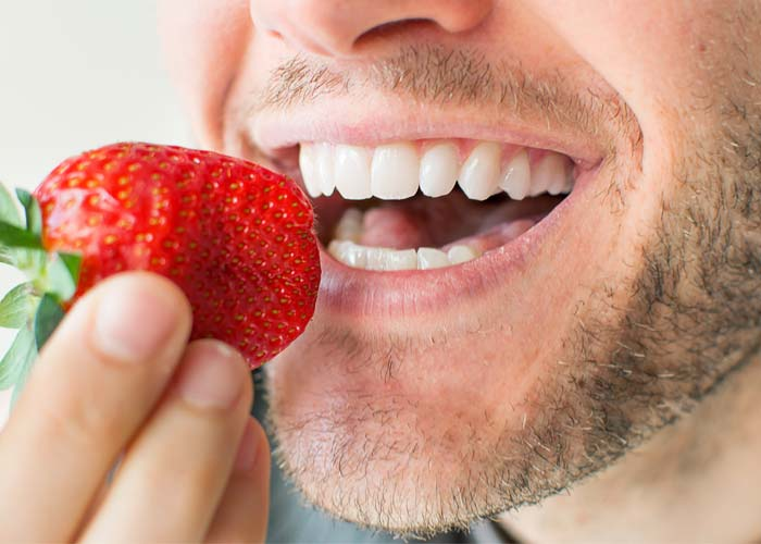 dental implants patients about to bite at a strawberry