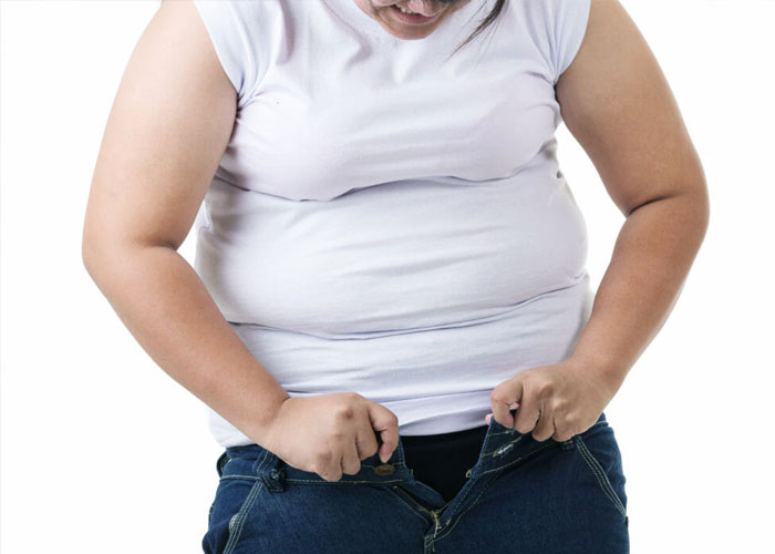obese woman trying to button jeans