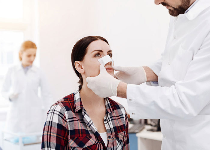 doctor taping a woman's nose after nose surgery