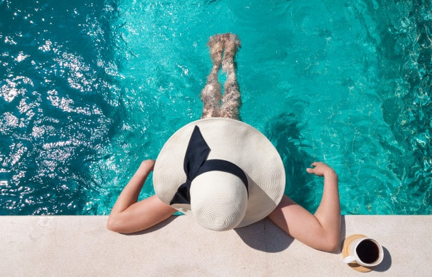 woman with a hat relaxing in a pool without swimming in summer