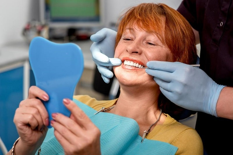 woman sitting in a dentist's chair looking in a mirror while her dentures are being checked by the dentist