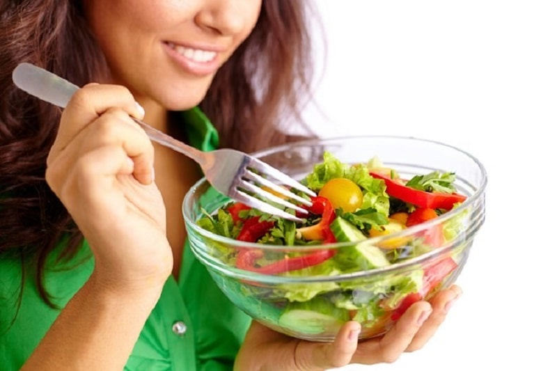 woman eating green salad out of a bowl