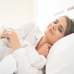 woman resting in bed after liposuction to recover faster