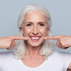 woman with false teeth pointing to her dentures