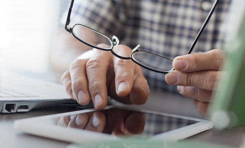 man working with a tablet while holding his eyeglasses in hand
