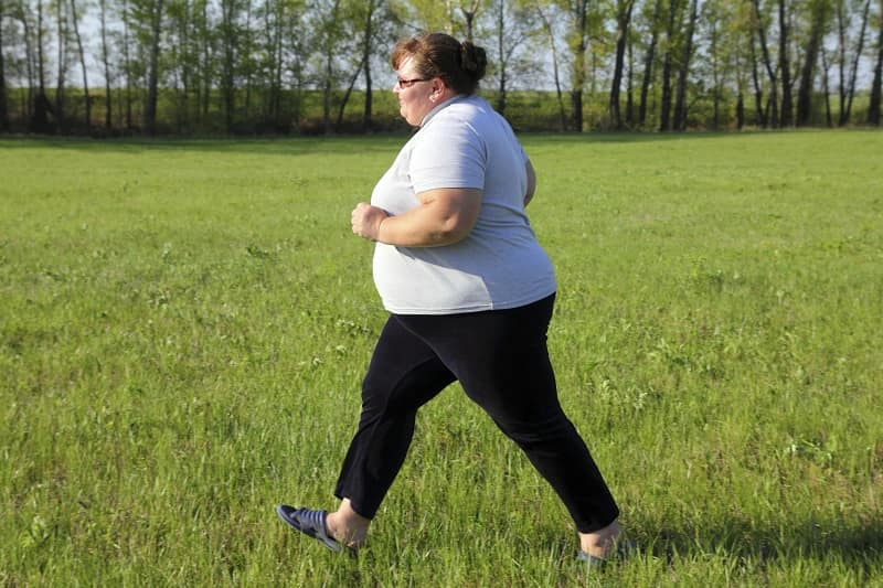 obese woman taking a walk in the park