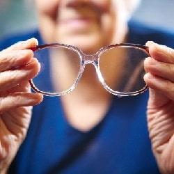 elderly woman holding eye-glasses