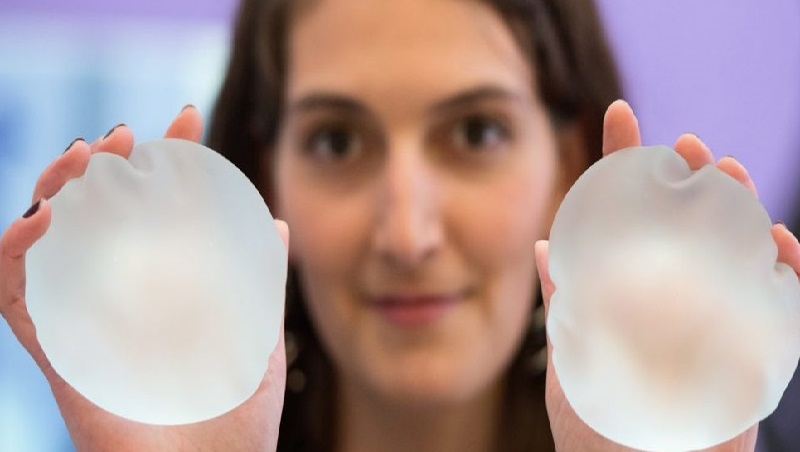 woman holding breast implants in her hands