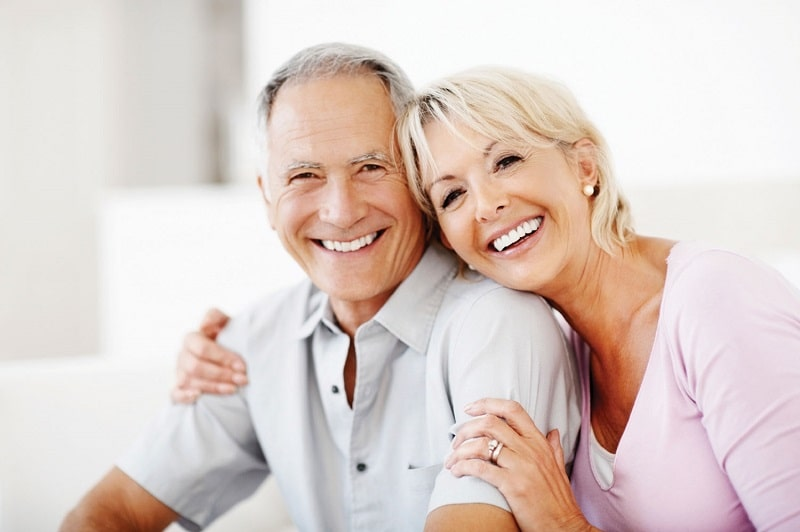 happy old couple with dentures ans bright smiles